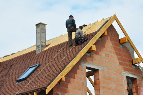 Roofing Construction and Building New Brick House with Modular Chimney, Skylights, Attic, Dormers and Eaves Exterior. Roofers Install, Repair Asphalt Shingles or Bitumen Tiles on the Rooftop Outdoor.